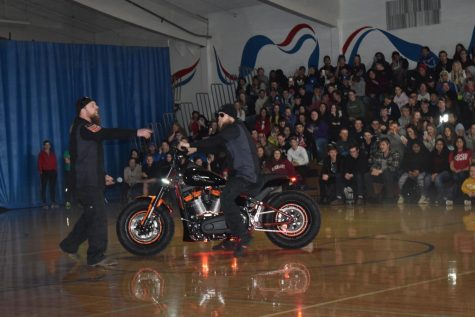 Harley Davidson workers rev across the SWHS gym to show off thier collaboration with high school students, in preparation for local project.