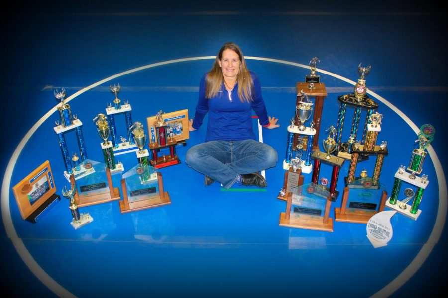 Celebrated+girls+wrestling+coach+Barb+Morgan+sits%2C+surrounded+by+her+trophies.+Her+newest+prize+celebrates+her+efforts+as+coach+for+the+entire+region.+