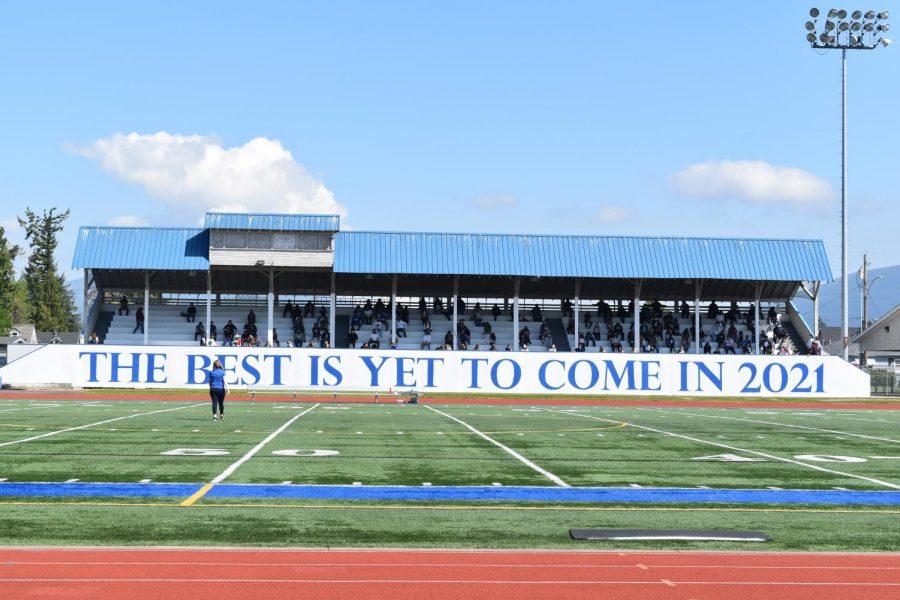 Seniors socially distance in Civic Stadium for their senior year photo.