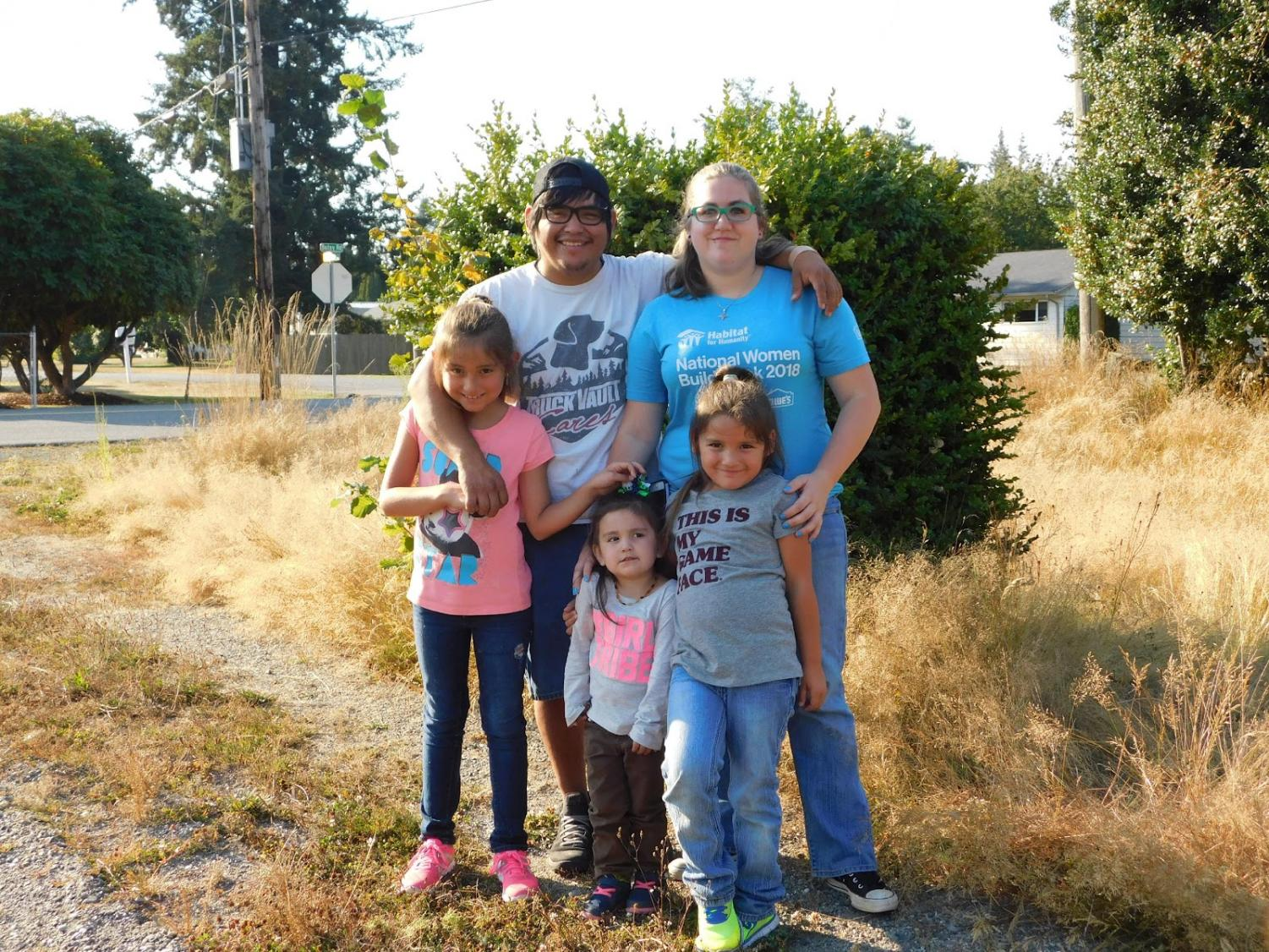 Local family stands at the site of their future home soon to be built by SWHS students. Courtesy of Habitat for Humanity