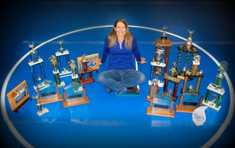 Celebrated girls wrestling coach Barb Morgan sits, surrounded by her trophies. Her newest prize celebrates her efforts as coach for the entire region.